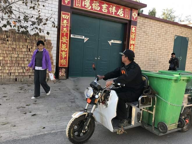 ایک مقامی شخص تین پہیوں والی مخصوص گاڑی پر کچرے اکٹھا کر رہا ہے۔