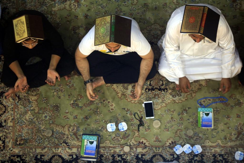 عراقی شیعہ مسلمان کوفہ کی جامع مسجد میں عبادت کے دوران قرآن پاک سر پر رکھے ہوئے ہیں(اے ایف پی)