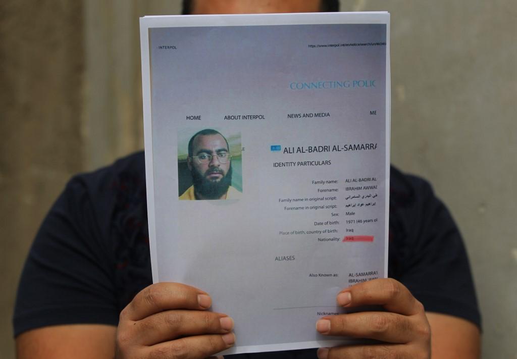 ایک شخص عراقی حکام کی جانب سے چھ فروری، 2018 کو جاری ہونے والا ابو بکر البغدادی کا پروفائل دکھا رہا ہے(اے ایف پی)