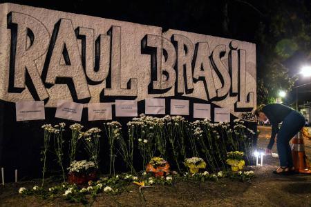 ایک خاتون حملے میں ہلاک ہونے والوں کی یاد میں شمع روشن کرتے ہوئے۔ تصویر: اے ایف پی