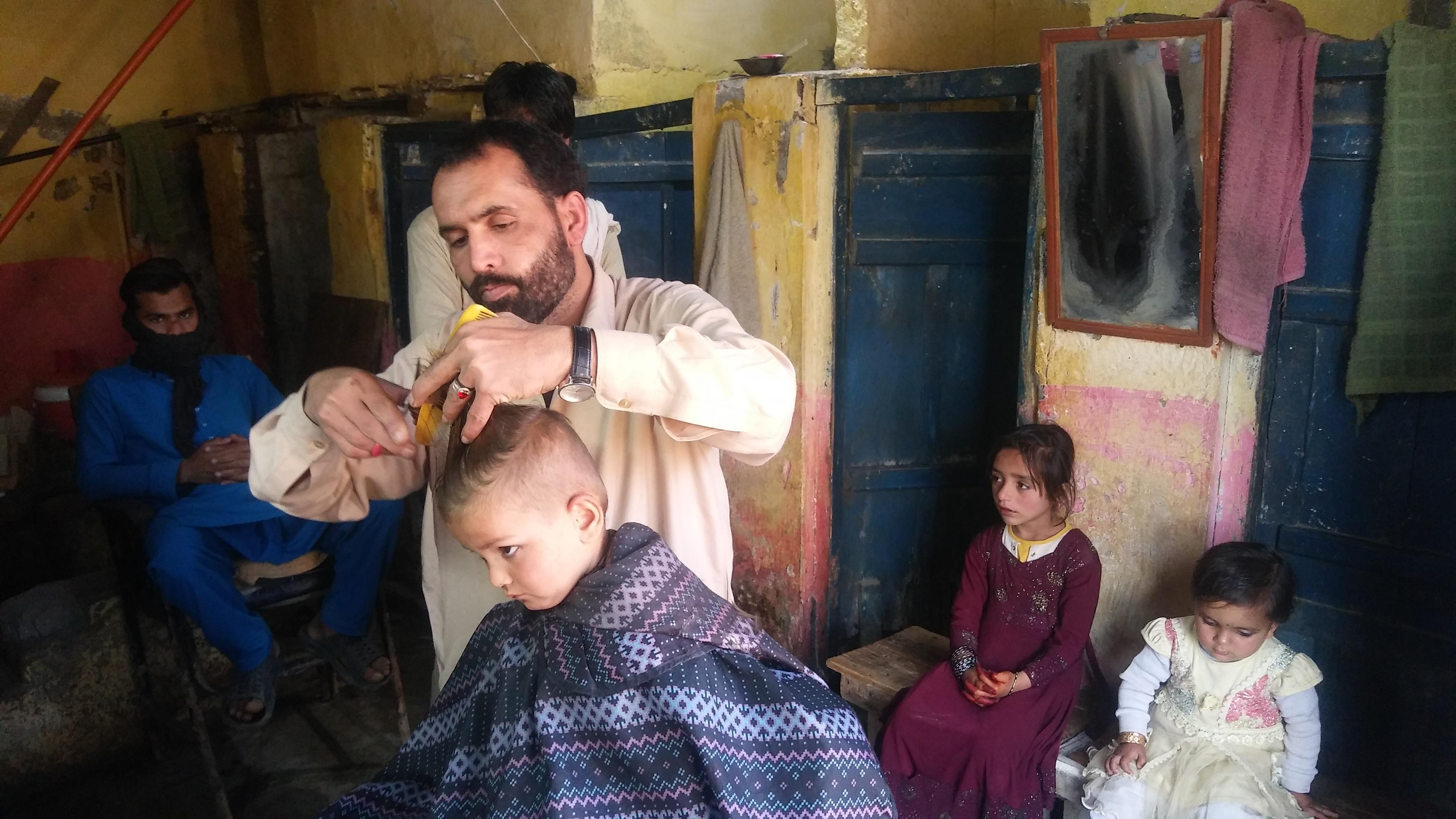 ہری پور کے کیمپ میں نائی ایک افغان بچے کے بال کاٹ رہا ہے۔ تصویر امداد حسین