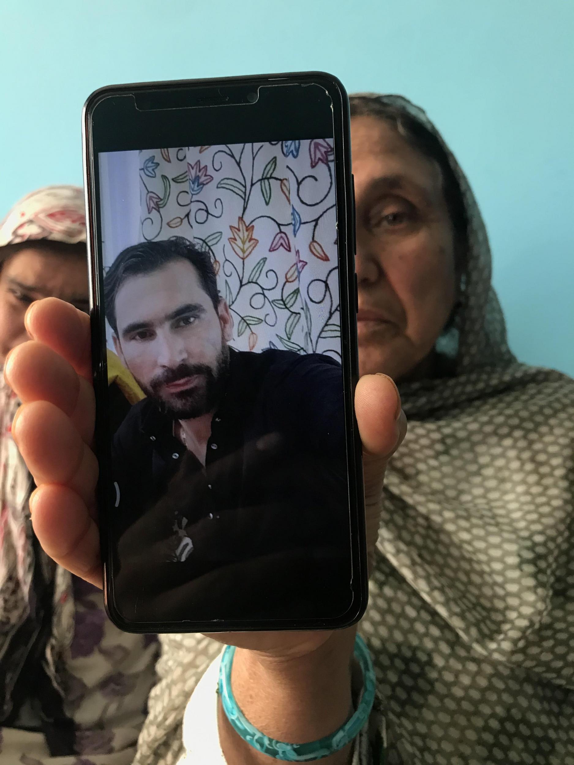 راجہ بیگم اپنے بیٹے عامر خان کی تصویر دکھاتے ہوئے (زبیر صوفی/ دی انڈپینڈنٹ)