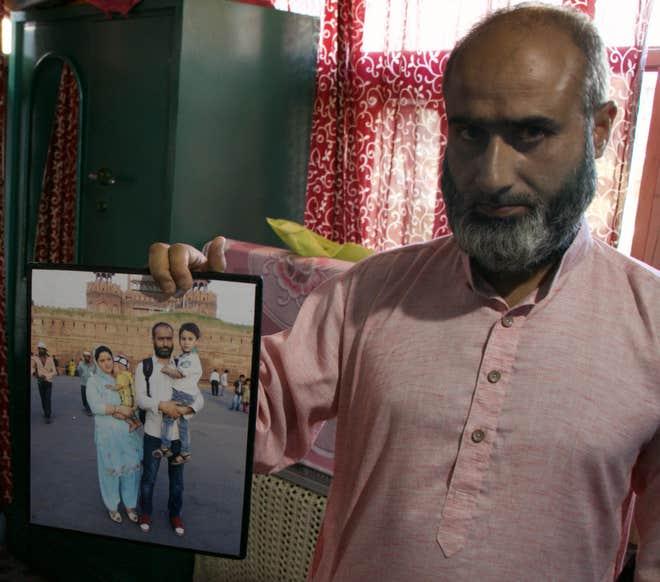 رفیق شگو اپنی بیوی فہمیدہ اور بچوں کی تصویر دکھا رہے ہیں (زبیر صوفی/ دی انڈپینڈنٹ)