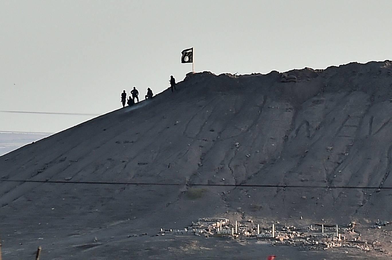 6 اکتوبر 2014 کو لی گئی اس تصویر میں داعش کے شدت پسند شامی علاقے کوبانی کی ایک پہاڑی پر اپنا جھنڈا لہراتے ہوئے۔ تصویر: اے ایف پی